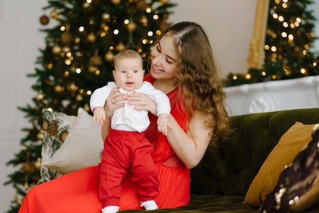 Eine junge stilvolle mutter in einem roten kleid hält ihren kleinen sohn in den armen neben dem weihnachtsbaum