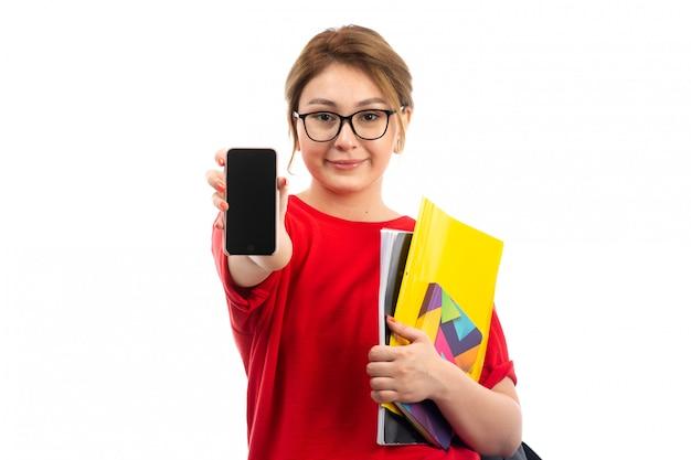 Eine junge studentin der vorderansicht in den schwarzen jeans des roten t-shirts, die hefte hält, die smartphone auf dem weiß zeigen