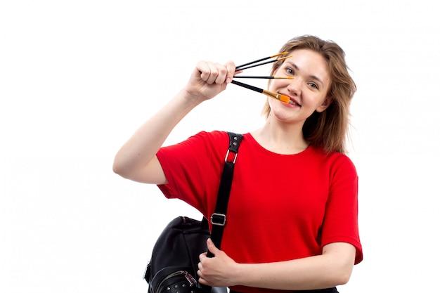 Eine junge studentin der vorderansicht in der schwarzen tasche des roten hemdes, die pinsel hält, die auf dem weiß lächeln