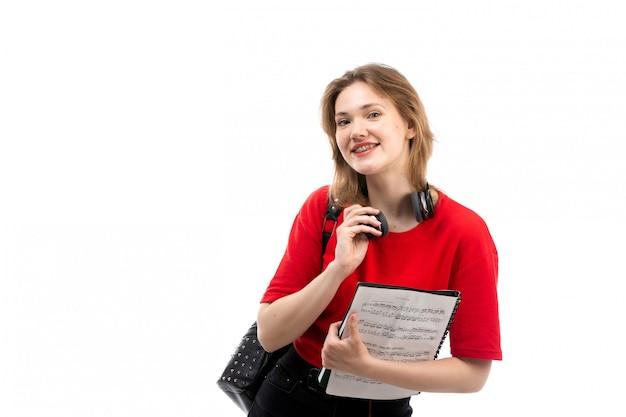 Eine junge studentin der vorderansicht in der schwarzen tasche des roten hemdes mit den schwarzen kopfhörern, die musik hören, die das copybook auf dem weiß hält