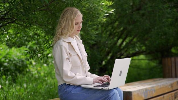 Eine junge studentin sitzt mit einem laptop auf einer parkbank. schöne blonde frau arbeitet für einen laptop auf einem hintergrund von grünen bäumen. arbeiten im freien. 4k uhd