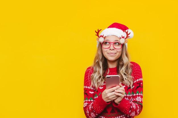 Eine junge süße frau in einer weihnachtspullover-hutbrille mit handy in den händen, die wegschaut