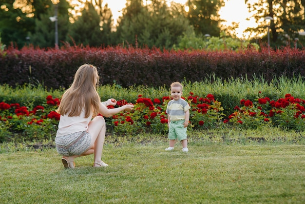 Eine junge süße mutter hilft und bringt ihrem kleinen sohn bei, seine ersten schritte während des sonnenuntergangs im park auf dem gras zu machen.