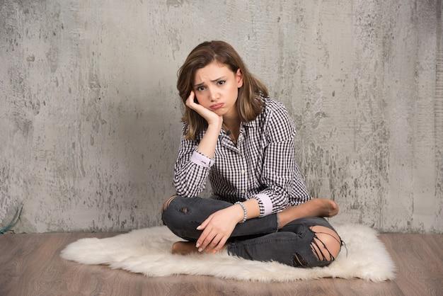 Eine junge traurige frau im karierten hemd, die ihre wangen durchbrennt.