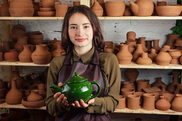 Eine junge und fröhliche frau modelliert aus ton. der töpfer arbeitet in einer töpferwerkstatt mit ton. das konzept der töpferei und kreativität