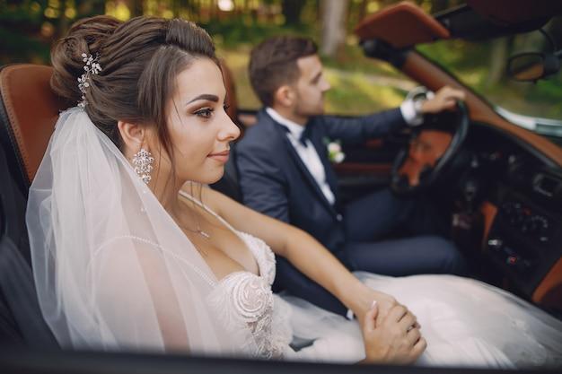 Eine junge und schöne braut sitzt in einem auto mit ihrem ehemann
