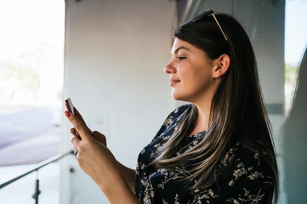Eine junge und schöne frau benutzt das smartphone, schreibt eine nachricht oder schaut sich die sozialen netzwerke an.