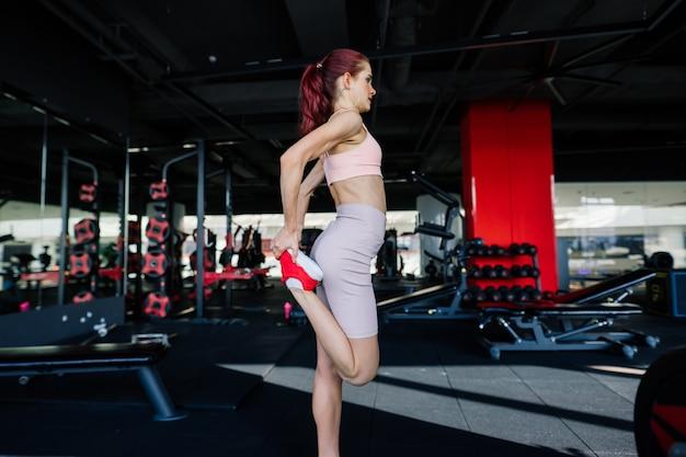 Eine junge und schöne frau trainiert mit einer langhantel im fitnessstudio. posieren mit elementen für das training