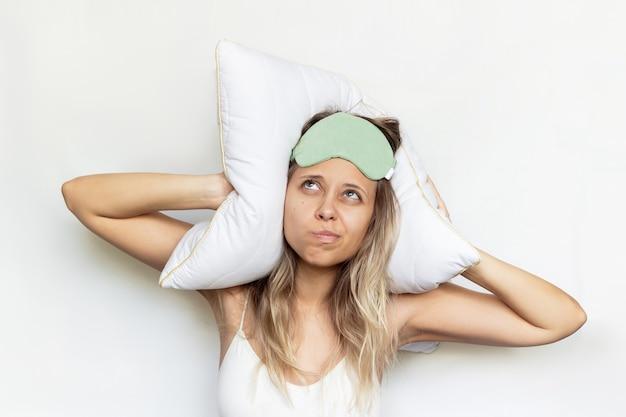 Eine junge unzufriedene frau in einer grünen schlafmaske bedeckt ihre ohren mit einem kissen laute nachbarn