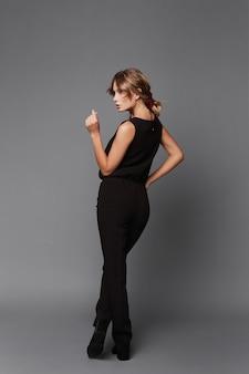 Eine junge vorbildliche frau in einer schwarzen hose und bluse, die mit ihrem rücken auf dem grauen hintergrund aufwirft