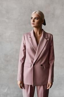 Eine junge vorbildliche frau mit blondem haar und perfektem make-up in einem rosa anzug, der drinnen aufwirft