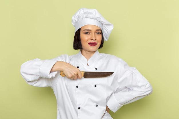 Eine junge weibliche köchin der vorderansicht im weißen kochanzug und im kappenhaltemesser auf der grünen wanddamenarbeitsnahrungsmittelküchenfarbe