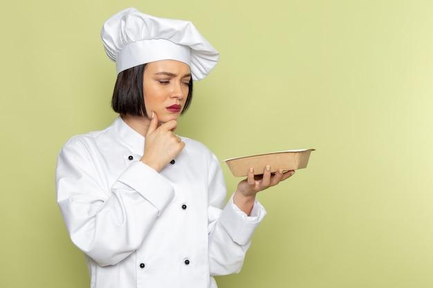 Eine junge weibliche köchin der vorderansicht im weißen kochanzug und im kappenhaltepaket mit denkendem ausdruck auf der grünen wanddamenarbeitsnahrungsmittelküchenfarbe