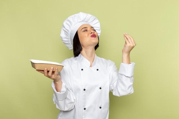 Eine junge weibliche köchin der vorderansicht im weißen kochanzug und im kappenhaltepaket mit entzücktem ausdruck auf der farbe der grünen wanddamenarbeitsnahrungsmittelküche