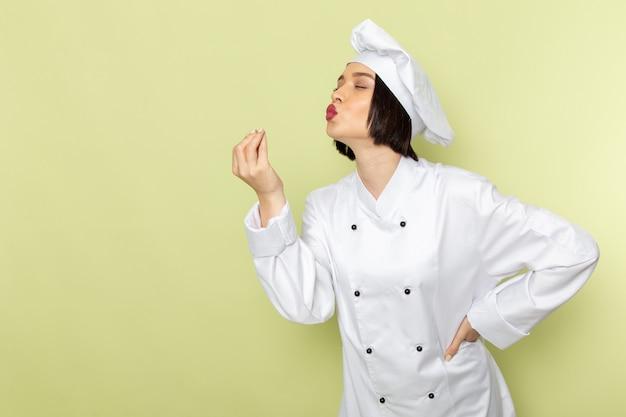Eine junge weibliche köchin der vorderansicht im weißen kochanzug und in der kappe, die die leckere geste auf der grünen wanddamenarbeitslebensmittelküchenfarbe aufwirft und zeigt