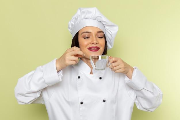 Eine junge weibliche köchin der vorderansicht im weißen kochanzug und in der kappe, die eine leere tasse an der grünen wand halten