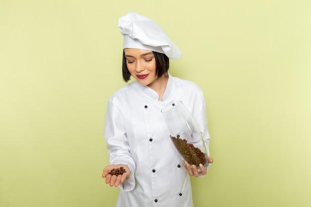 Eine junge weibliche köchin der vorderansicht im weißen kochanzug und in der kappe, die glas mit kaffeesamen auf der grünen wanddamenarbeitslebensmittelküchenfarbe hält