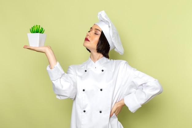 Eine junge weibliche köchin der vorderansicht im weißen kochanzug und in der kappe, die grüne pflanze auf der grünen wanddamenarbeitslebensmittelküchenfarbe halten