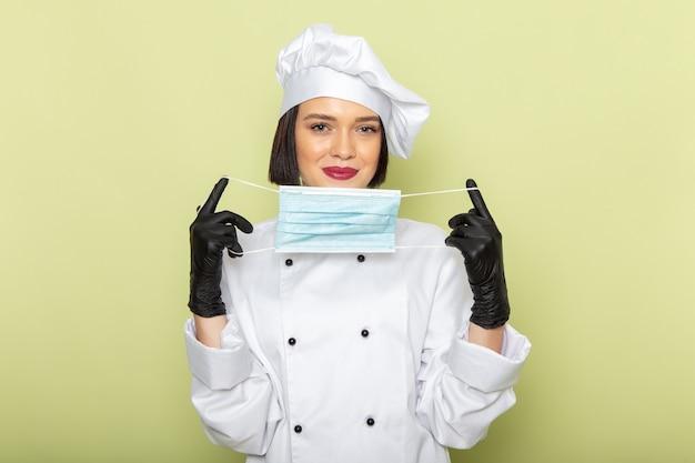 Eine junge weibliche köchin der vorderansicht im weißen kochanzug und in der kappe, die handschuhe und sterile maske auf der grünen wanddamenarbeitslebensmittelküchenfarbe tragen