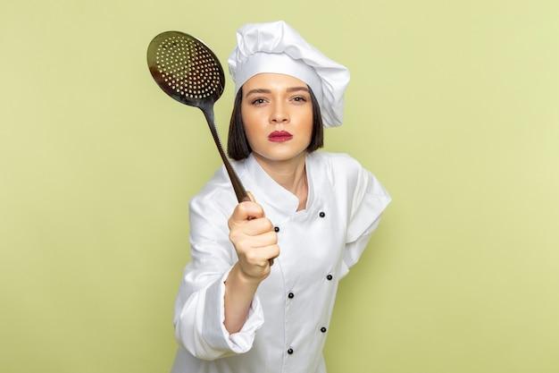 Eine junge weibliche köchin der vorderansicht im weißen kochanzug und in der kappe, die löffel hält, der auf der grünen wanddamenarbeitslebensmittelküchenfarbe bedroht