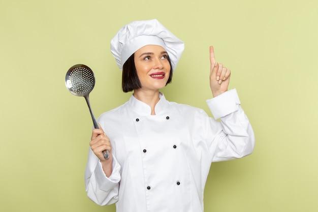 Eine junge weibliche köchin der vorderansicht im weißen kochanzug und in der kappe, die löffel mit träumendem ausdruck auf der grünen wanddamenarbeitslebensmittelküchenfarbe hält