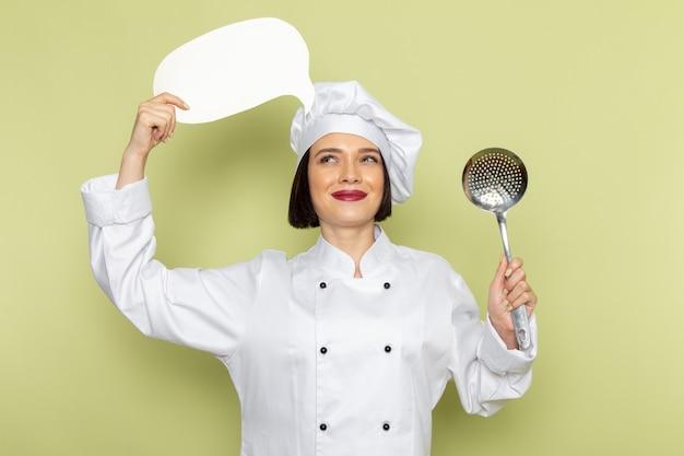 Eine junge weibliche köchin der vorderansicht im weißen kochanzug und in der kappe, die löffel und weißes zeichen auf der grünen wanddamenarbeitslebensmittelküchenfarbe halten