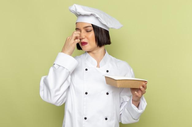 Eine junge weibliche köchin der vorderansicht im weißen kochanzug und in der kappe, die paket hält, das ihre nase auf der farbe der grünen wanddamenarbeitsnahrungsmittelküche schließt