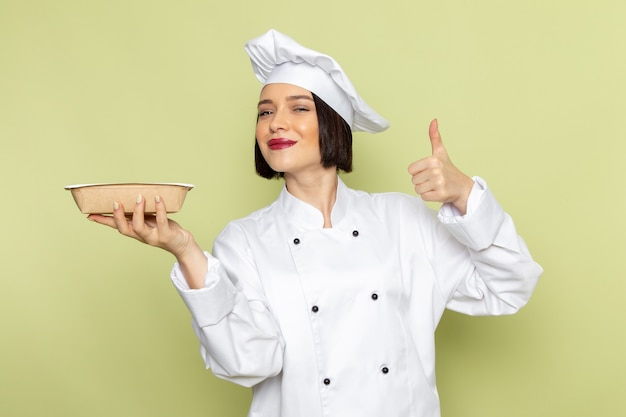 Eine junge weibliche köchin der vorderansicht im weißen kochanzug und in der kappe, die schüssel mit lächeln auf der grünen wand hält