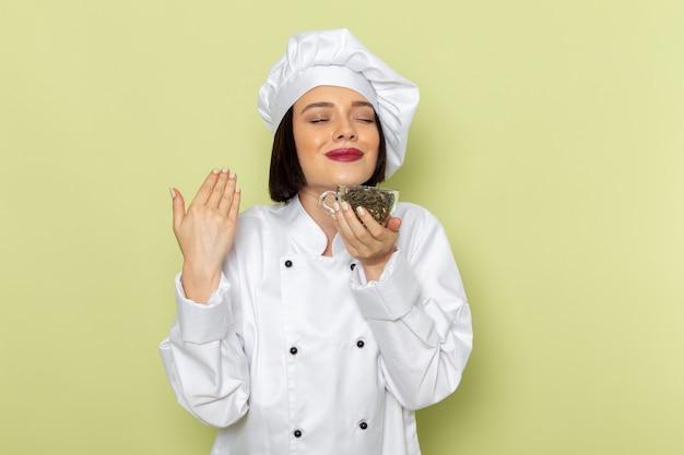 Eine junge weibliche köchin der vorderansicht im weißen kochanzug und in der kappe, die tasse mit getrocknetem tee an der grünen wand hält