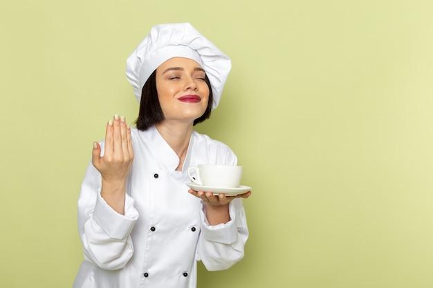 Eine junge weibliche köchin der vorderansicht im weißen kochanzug und in der kappe, die tasse mit lächeln auf der grünen wanddamenarbeitslebensmittelküchenfarbe hält