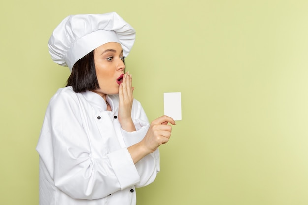 Eine junge weibliche köchin der vorderansicht im weißen kochanzug und in der kappe, die weiße karte auf der grünen wanddamenarbeitslebensmittelküchenfarbe halten
