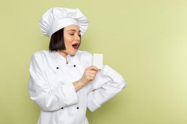 Eine junge weibliche köchin der vorderansicht im weißen kochanzug und in der kappe, die weiße karte mit lächeln auf der grünen wanddamenarbeitslebensmittelküchenfarbe halten