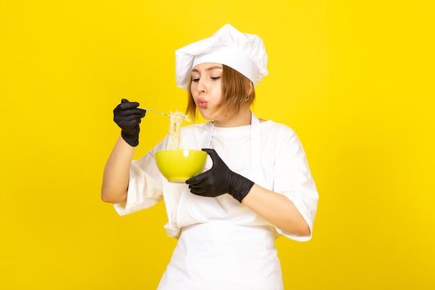 Eine junge weibliche köchin der vorderansicht im weißen kochanzug und in der weißen kappe in den schwarzen handschuhen, die grünen teller halten, der spaghetti auf dem gelben mischt