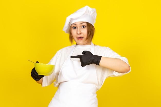 Eine junge weibliche köchin der vorderansicht im weißen kochanzug und in der weißen kappe in den schwarzen handschuhen, die grünen teller mit spaghetti auf dem gelben halten