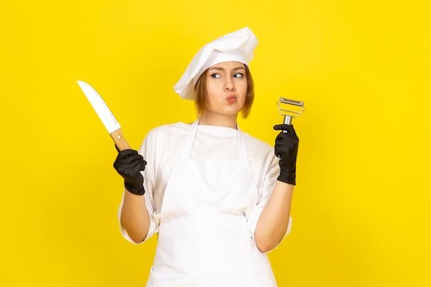 Eine junge weibliche köchin der vorderansicht im weißen kochanzug und in der weißen kappe in den schwarzen handschuhen, die messer und gemüsereiniger auf dem gelben halten
