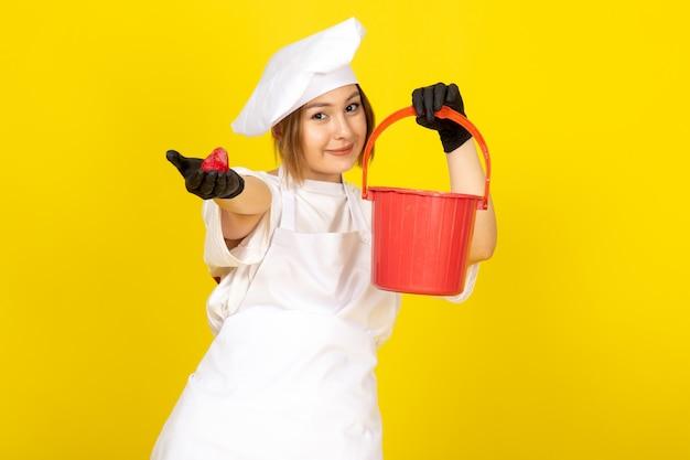 Eine junge weibliche köchin der vorderansicht im weißen kochanzug und in der weißen kappe in den schwarzen handschuhen, die roten korb und erdbeere auf dem gelben halten