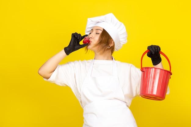 Eine junge weibliche köchin der vorderansicht im weißen kochanzug und in der weißen kappe in den schwarzen handschuhen, die roten korb und erdbeere halten, die es auf dem gelben küssen