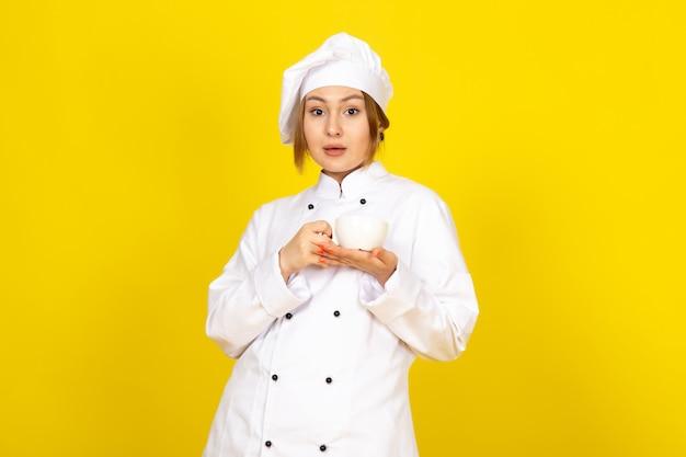 Eine junge weibliche köchin der vorderansicht im weißen kochanzug und in der weißen kappe trinkend, die tasse kaffee auf dem gelben hält