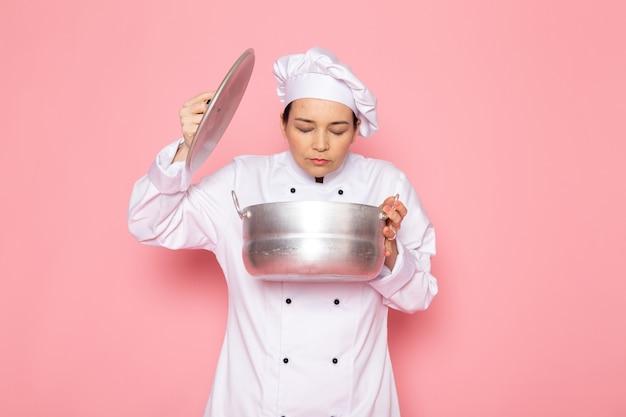 Eine junge weibliche köchin der vorderansicht in der weißen kappe des weißen kochanzugs, die das halten des silbernen topfes riecht, der innen riecht