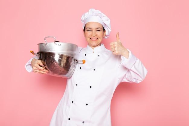 Eine junge weibliche köchin der vorderansicht in der weißen kappe des weißen kochanzugs, die das lächeln der silbernen topfpfannen hält