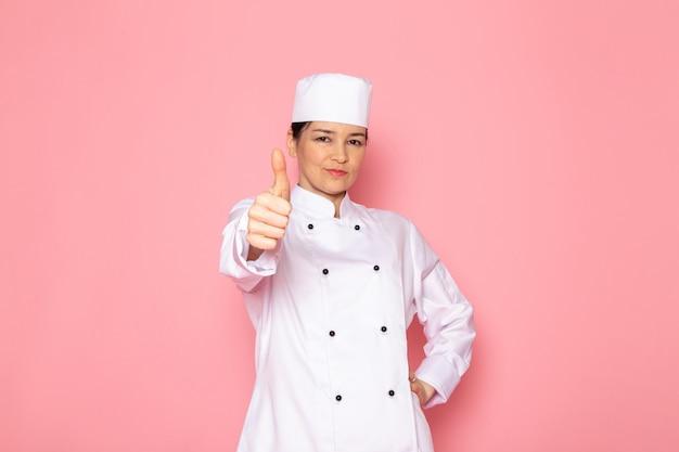 Eine junge weibliche köchin der vorderansicht in der weißen kappe des weißen kochanzugs, die entzückenden lächelnden ausdruck aufwirft