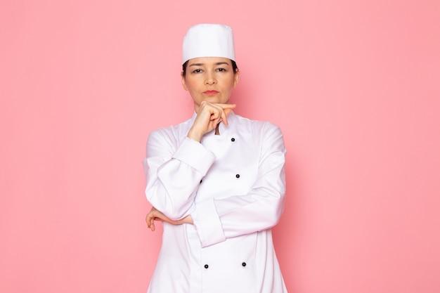Eine junge weibliche köchin der vorderansicht in der weißen kappe des weißen kochanzugs, die tief denkenden ausdruck aufwirft