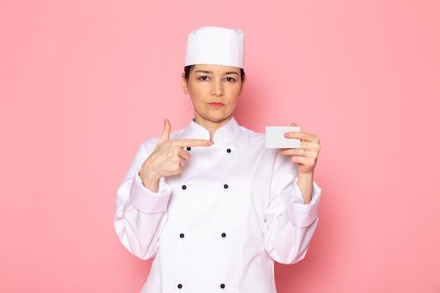 Eine junge weibliche köchin der vorderansicht in der weißen kappe des weißen kochanzugs, die weiße karte hält