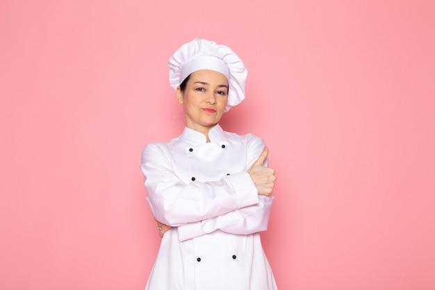 Eine junge weibliche köchin der vorderansicht in der weißen kappe des weißen kochanzugs lächelnd posierend glücklich