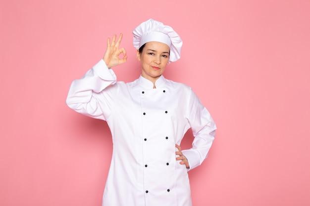 Eine junge weibliche köchin der vorderansicht in der weißen kappe des weißen kochanzugs lächelnd posierend