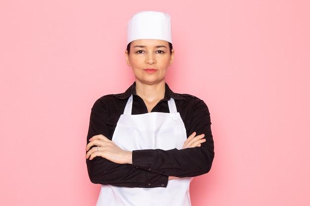 Eine junge weibliche köchin der vorderansicht in der weißen kappe des weißen kochumhangs des schwarzen hemdes, die halbes lächeln aufwirft