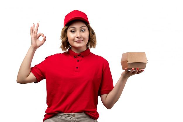 Eine junge weibliche kurierfrau der vorderansicht des lebensmittellieferdienstes, der das lebensmittelpaket hält, das auf weiß lächelt