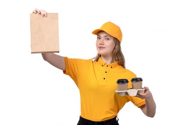 Eine junge weibliche kurierfrau der vorderansicht des lebensmittellieferdienstes lächelnd, die lebensmittelpaket und kaffeetassen auf weiß hält
