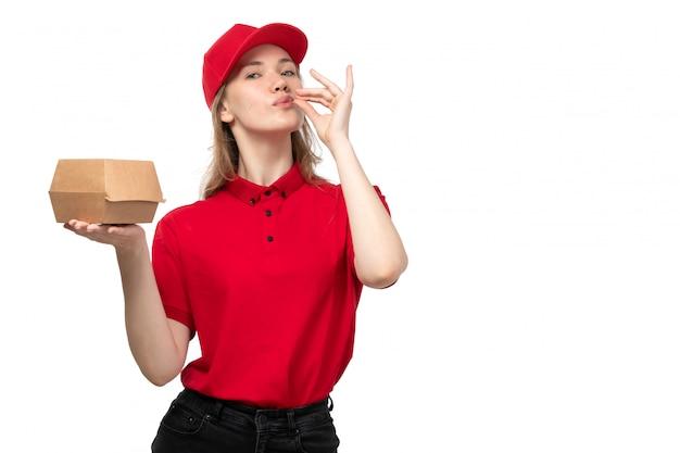 Eine junge weibliche kurierfrau der vorderansicht, die lächelndes haltepaket des lebensmittellieferservices mit essen zeigt, das leckeres zeichen auf weiß zeigt