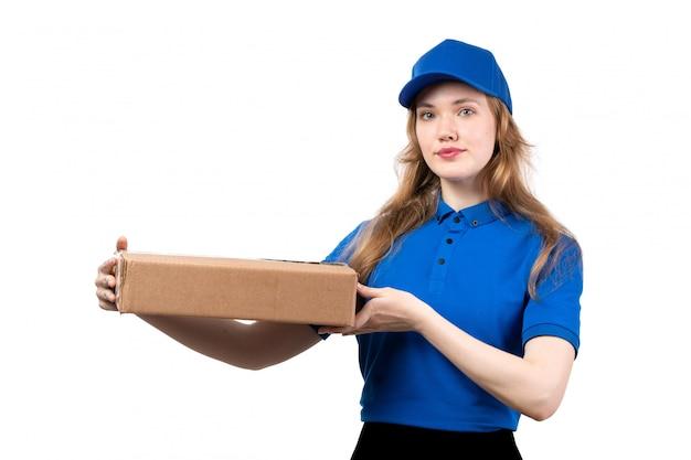 Eine junge weibliche kurierin der vorderansicht des weiblichen lieferservices des lebensmittellieferservices hält das lebensmittellieferpaket auf weiß